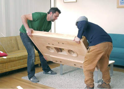 Two men holding table top as they flip it over