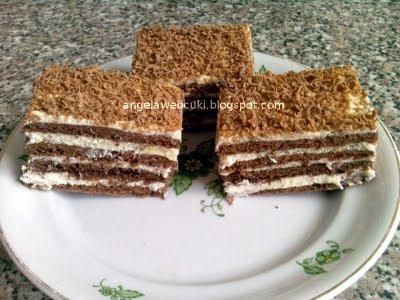 Kókuszkrémes szelet, kakaó tésztás sütemény, csokoládé reszelékkel a tetején.