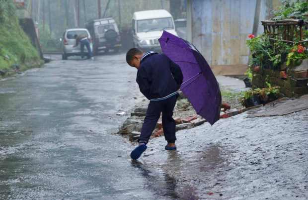 Indian Monsoon boy enjoying with umbrella