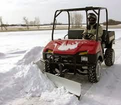 Small all-terrain vehicle plowing snow