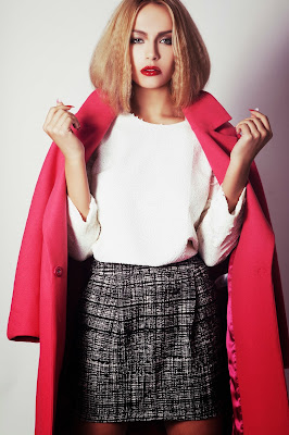 model poses for test shots for her agency with a coral oversized coat and faux bob hairstyle with a futuristic feel