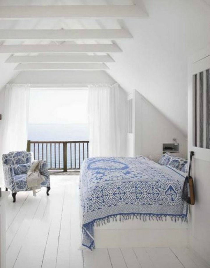 Coastal blue and white bedroom with an ocean view