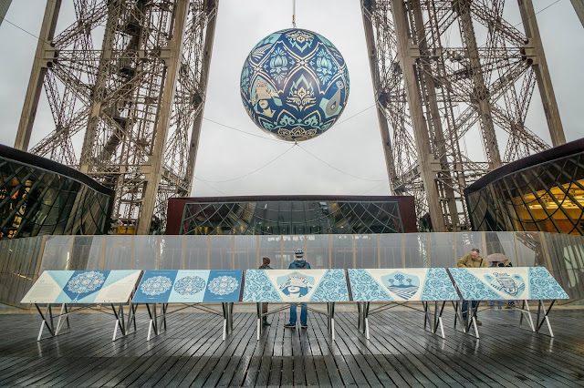 "Shepard Fairey is currently in Paris, France where he just unveiled his latest installation ""Earth Crisis"", an environmentally themed giant sphere hung between the first and second floor of the legendary Eiffel Tower."