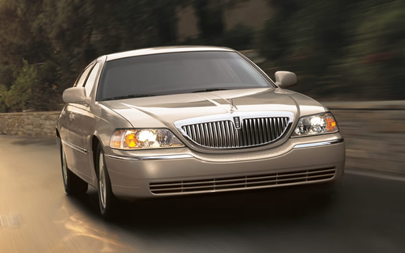 Front 3/4 view of silver 2011 Lincoln Town Car driving with lights on