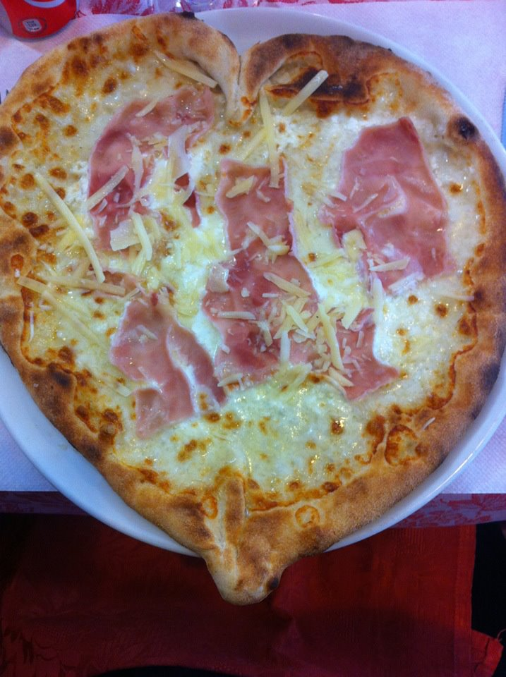 pizzaioli che bakkagliano le tipe facendo pizze a forma di cuore