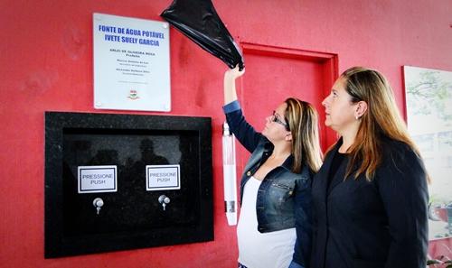 Filhas da funcionária pública homenageada, Elaine e Jaqueline Garcia Alves descerram a placa de inauguração da fonte de água potável da Rodoviária