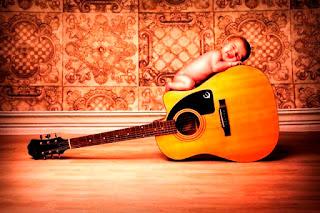 Foto bayi lucu tidur di atas gitar