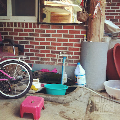 A water faucet surrounded by cleaning supplies and various items outside a home in South Korea.