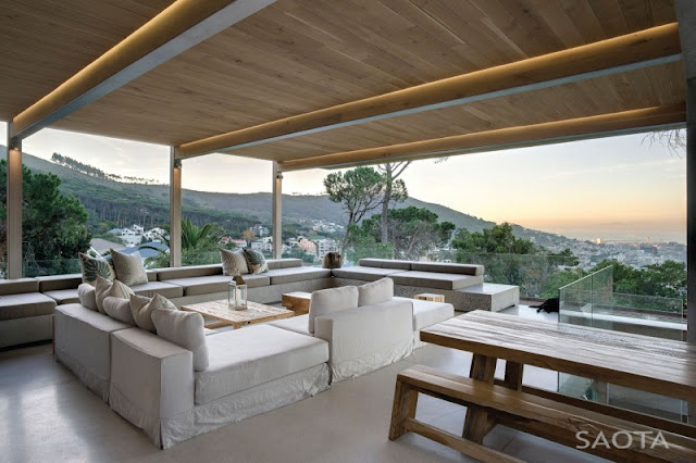 Photo of large covered terrace with outdoor sofas and other garden furniture