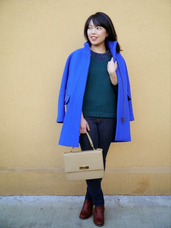 Cobalt blue cocoon coat worn with forest green pullover sweater, dark wash skinny jeans, cognac leather ankle boots, and a taupe top-handle bag.