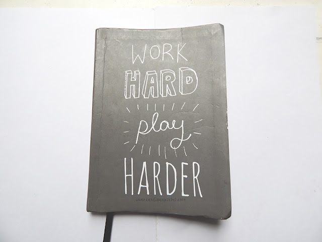 "light grey notebook with hand written text on the cover reading ""work hard play harder"""