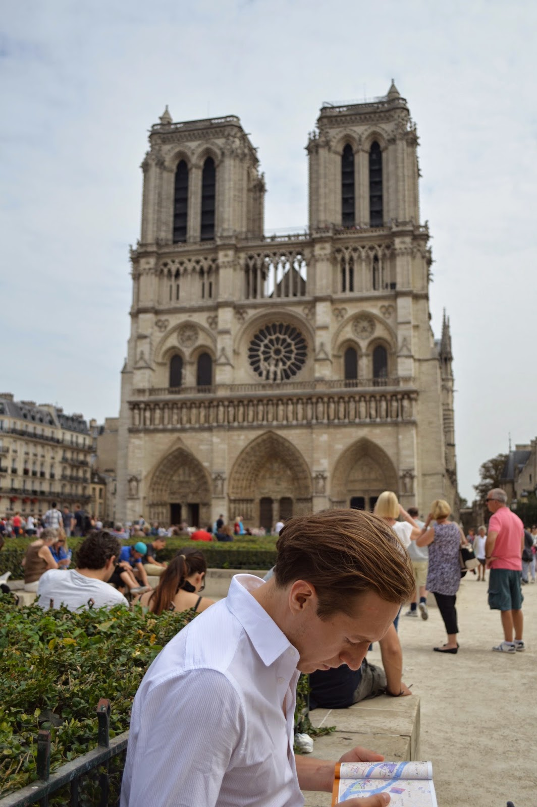 David reading a Paris guide in front of the Notre-Dame Cathedral.