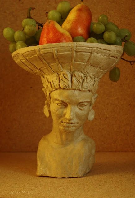 art, sculpture, sarah myers, stoneware, ceramic, escultura, arte, ceramica, fruit, centerpiece, centrepiece, arrangement, figurative, head, woman, basket, bearer, graceful, tranquil, beautiful, food, abundance, plenty, table, face, human, classic, pears, grapes