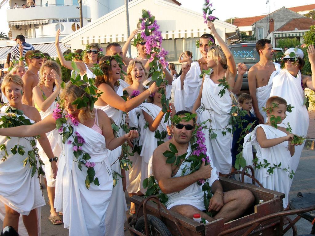 Grupa mladih ljudi obučena u rimske toge ukrašene cvećem