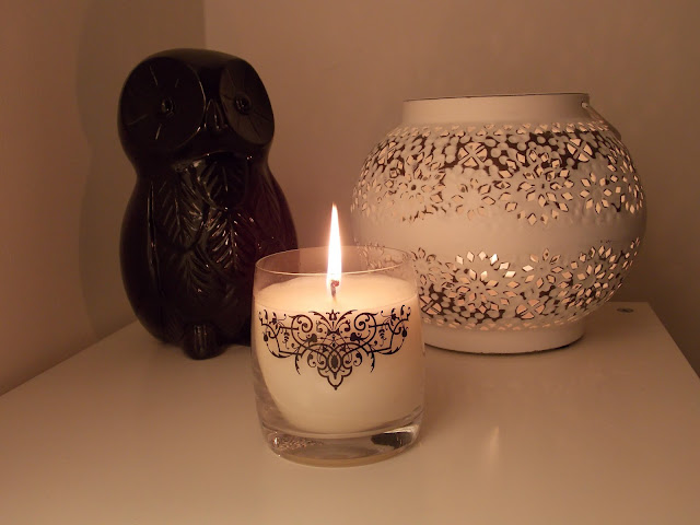 A Melt Scented Candle against a pale background at night