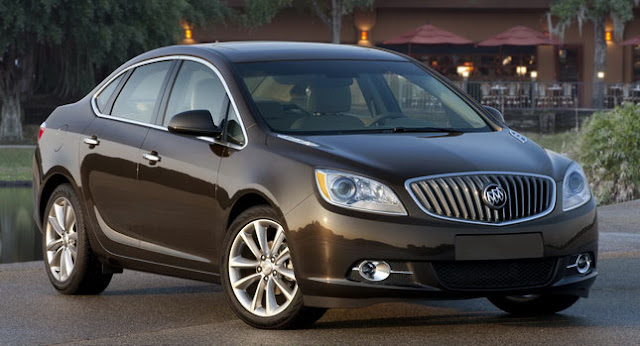Front 3/4 view of dark brown 2012 Buick Verano parked in resort setting