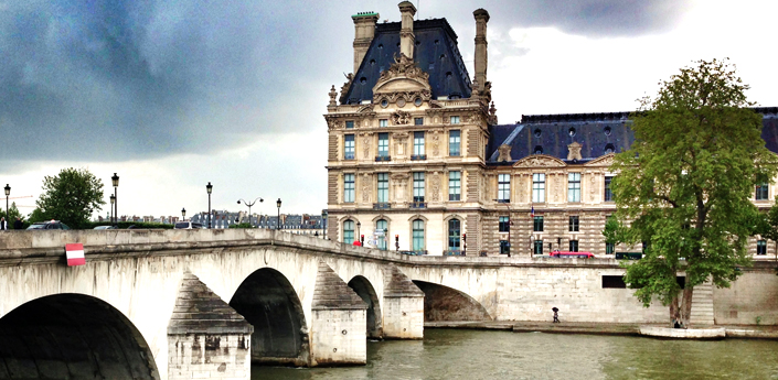 cycling to the Louvre palace along the sein in Paris France
