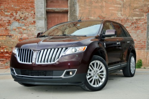 Front 3/4 view of dark red 2011 Lincoln MKX parked in front of brick building