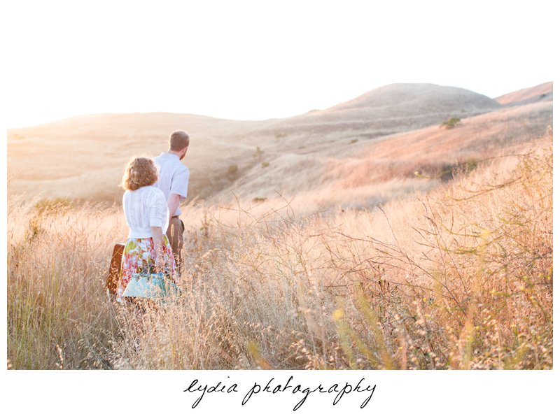 Bride and groom walking with picnic basket and luggage at lifestyle engagement portraits in the Bay Area of California