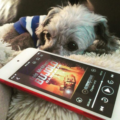 Murchie lays on a fuzzy, cream-coloured pillow, head down. His hair has been clipped short and he wears a blue and white striped t-shirt. In front of him is a red-bordered iPod with Barrayar's orange-tinted cover on its screen. It depicts a spaceship moving through an indistinct but presumably terrestrial landscape.