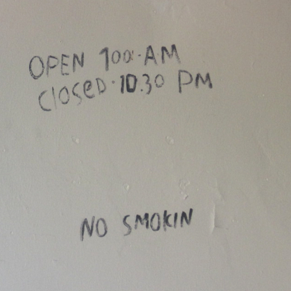 "Photograph of writing on a wall: ""OPEN 700 AM / CLOSED 1030 PM / NO SMOKIN"""