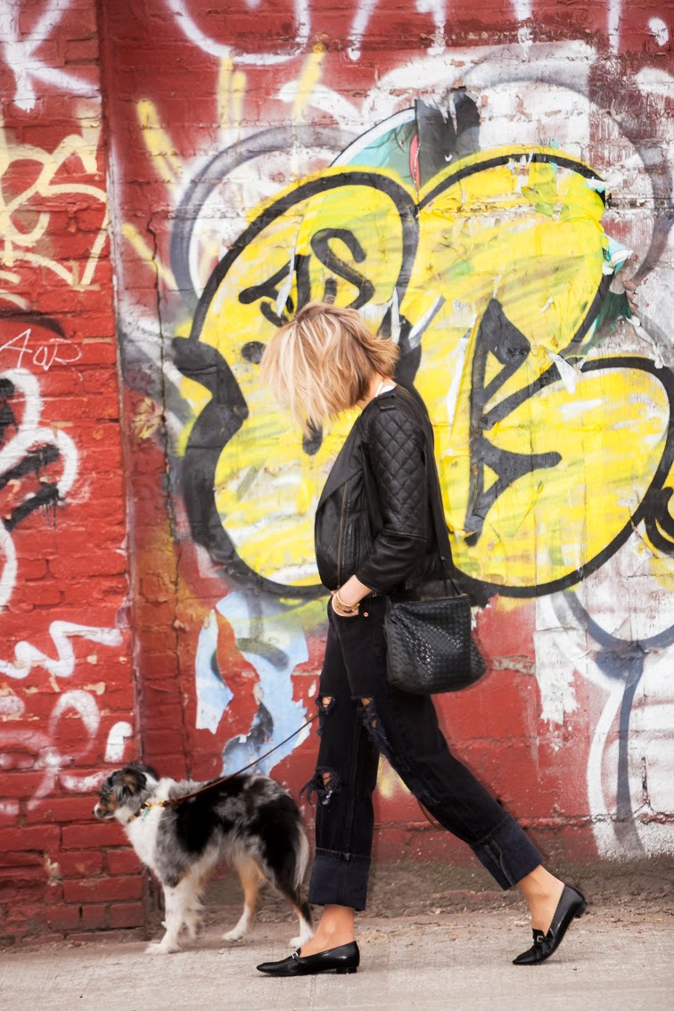 Graffiti wall, all black, quilted leather bomber jacket, Chanel loafers, Bottega Veneta intrecciato crossbody bag