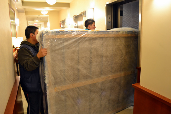 Movers helping load a mattress into the elevator