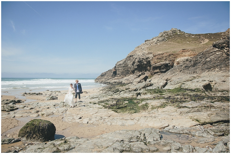 Bride and groom walk up the beach