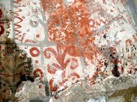 Detall de les pintures murals de color gris i vermell, que imiten les juntes dels murs i amb decoració de motius florals