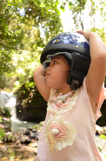 Kecil with helmet at the waterfall