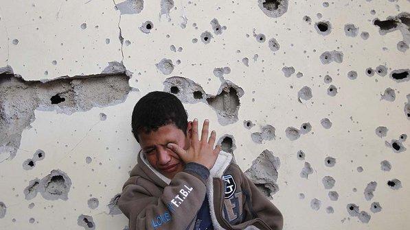 Garoto chora em sua casa danificada pelos ataques israelenses