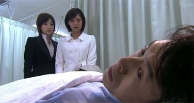 Misaki and Wakamura stand over her the bed where her father, played by Asano Kazuyuki ( 浅野和之 ) is resting at the hospital.