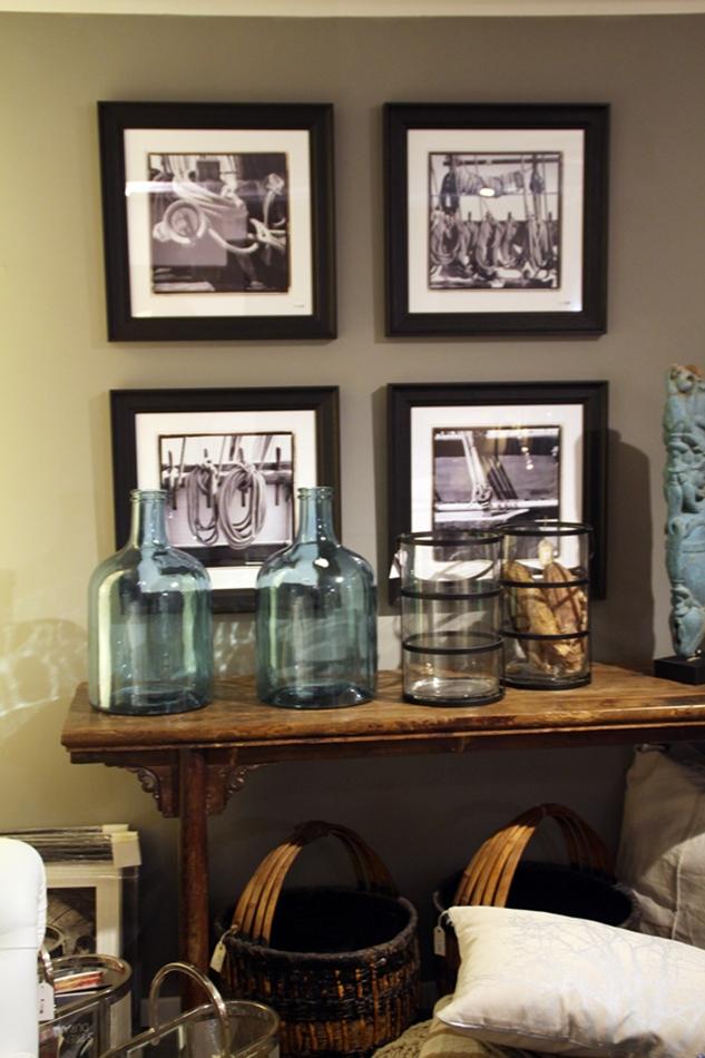 Kommode aus Holz mit blauen Flaschen und Bildern im Hintergrund