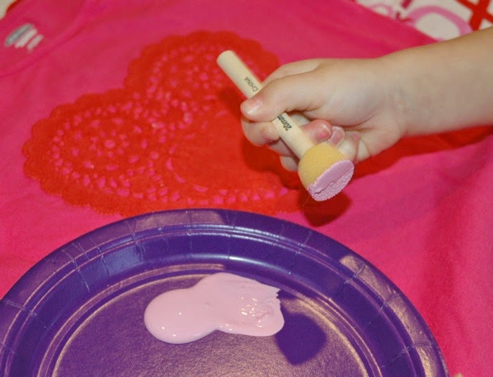 Using sponge brush to add paint to heart shirt