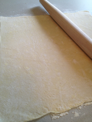 Image shows the dough being rolled into a rectangle
