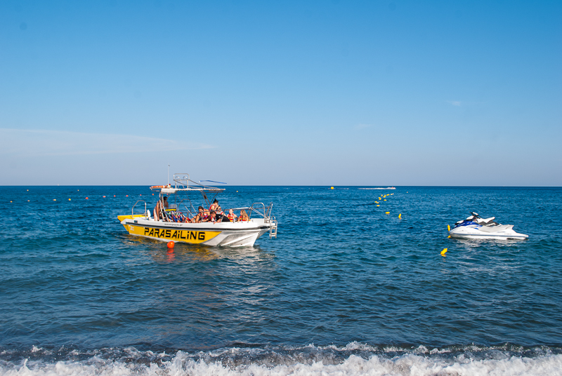 picture of the parasailing boat and jet ski on santorini perissa black beach