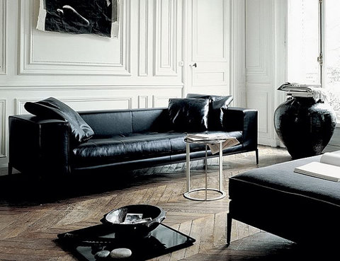 black leather sofa with black leather pillows, white molded walls and herringbone wood floors