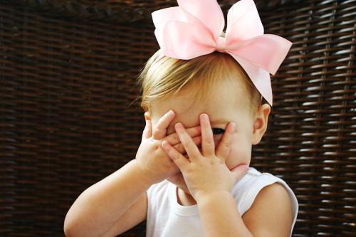 Foto de uma criança tímida, com as mãos na frente do rosto.