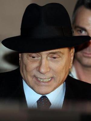 Silvio Berlusconi wearing a quite serious Borsalino hat