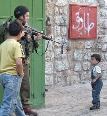 soldado terrorista de Israel aponta arma para criança palestina