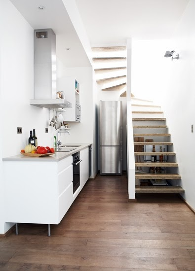 Small white kitchen under a staircase with a tall narrow fridge and stainless hood