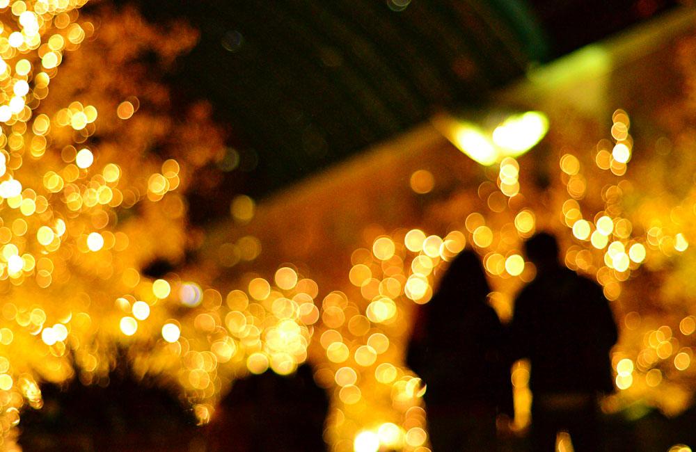 イルミネーションを歩く恋人同士の写真