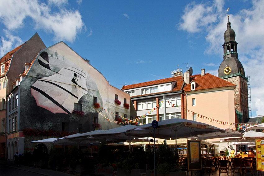 Praça com uma esplanada à sombra, a seguir os prédios e por detrás a torre da Catedral