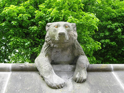 Statue of a bear looking over a ridged wall