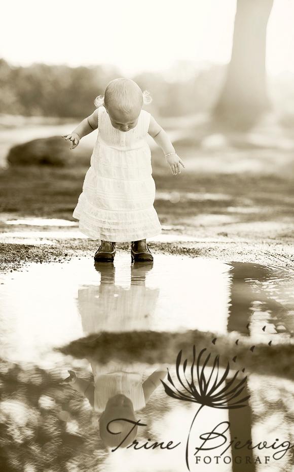 Liten jente speiler seg i sølepytt, barnebilder fra fotograf Trine Bjervig, tønsberg