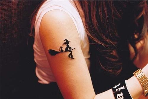 tatuaje tribal en el brazo de una chica de una bruja volando en su escoba con un gato