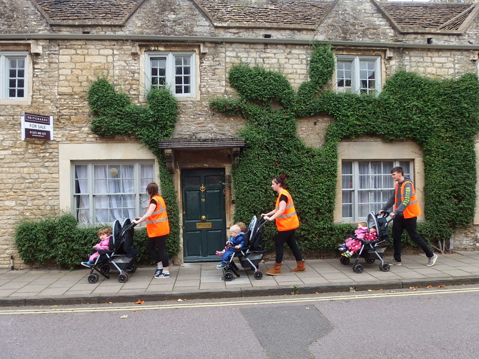 A parade of pushchairs go past a house clad in Cotoneaster in Corsham, Wiltshire