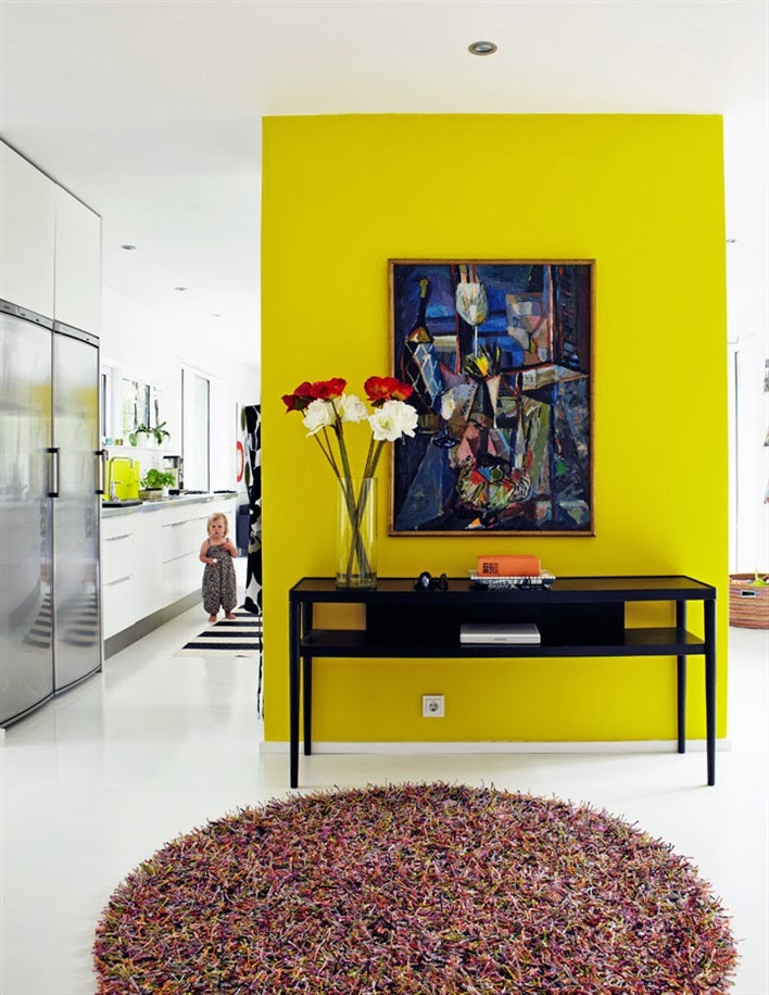 Bright yellow floating wall in a foyer of a modern home
