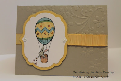 Sahara Sand card base with embossed flowers and yellow ribbon. Focal image is a bunny riding in an Easter Egg hot air balloon.