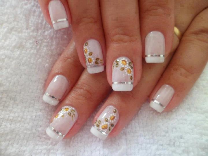 Bonito diseño con flores pintadas sobre las uñas.